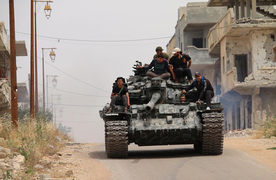 Боевики оппозиции управляют танком в удерживаемых повстанцами, 10 мая 2016 года.
