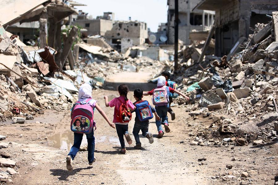 Сирийские школьники пробегают мимо сильно поврежденных зданий на восточной окраине Дамаска, по 30 апреля 2016 года.