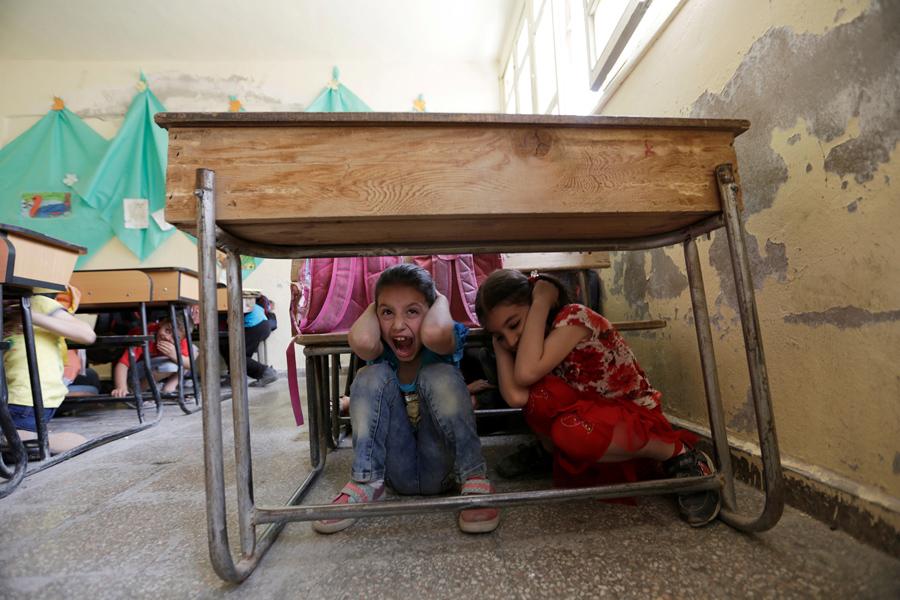 Детей в школах учат прятаться за парты во время бомбардировок.