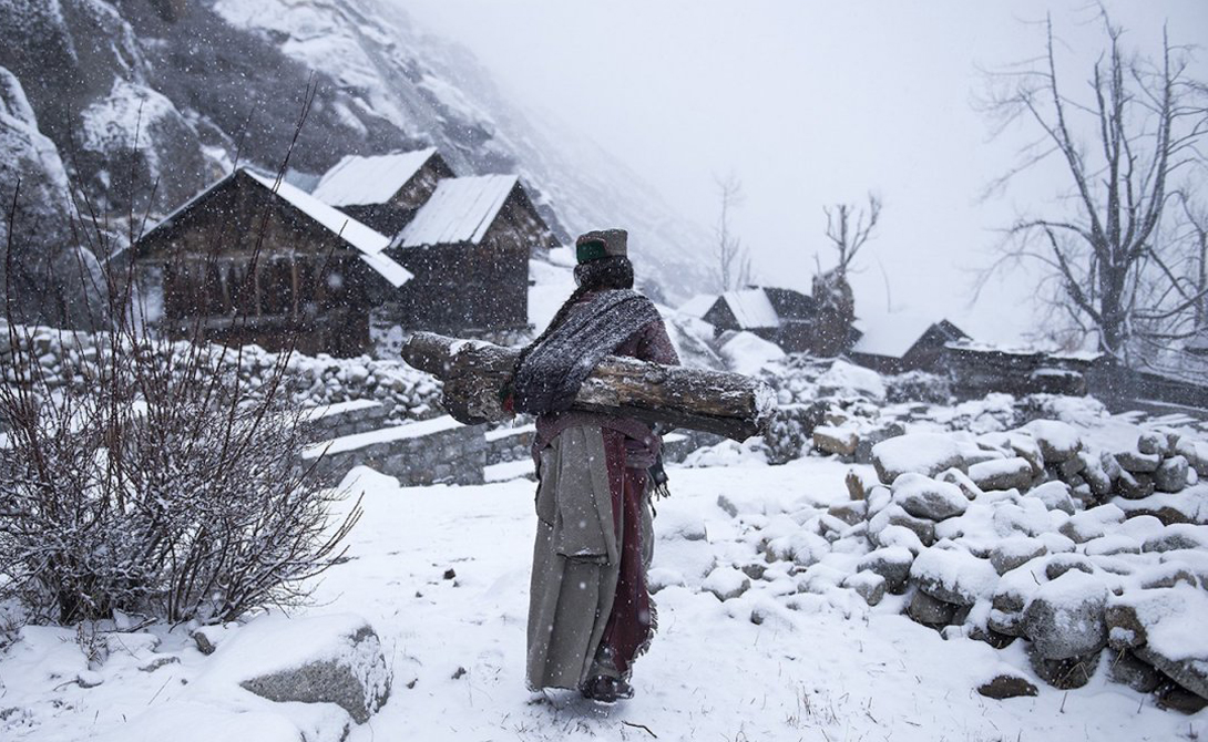 Женщина возвращается в свой дом, собрав дрова для отопления.