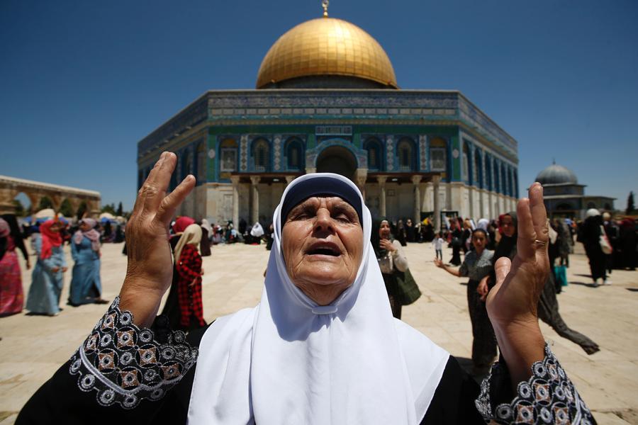 Палестинская женщина молится перед мечетью Аль-Акса в Иерусалиме для пятничных молитв священного для мусульман месяца Рамадан, 1 июля 2016 год