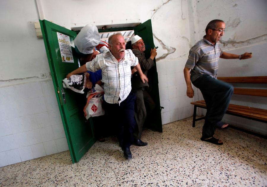 Палестинцы спешат получить пищу, приготовленную бесплатно во время священного месяца Рамадан в городе Хеврон на Западном берегу, 13 июня 2016 года.