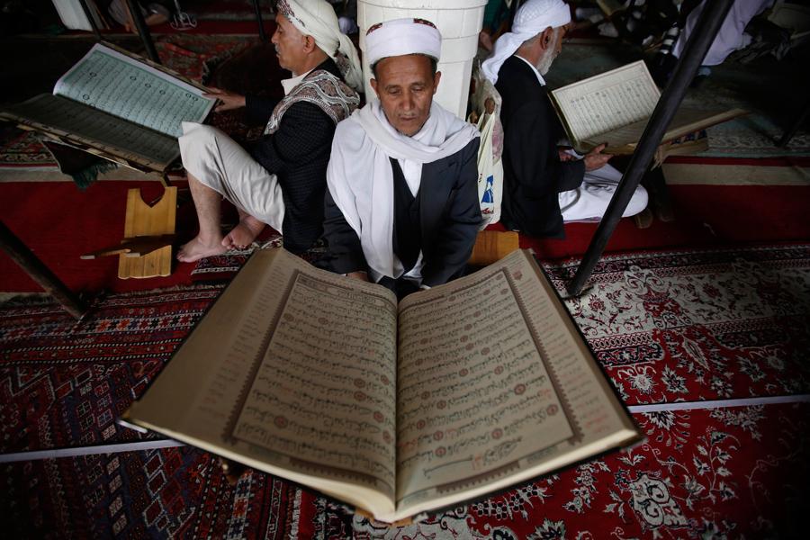 Мужчины читают священная книгу Коран в первый день месяца в Большой мечети, старого города Сана, Йемен, 6 июня 2016 года.