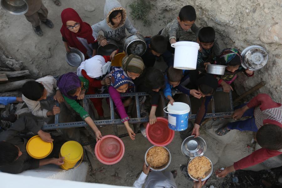 Афганские жители получают бесплатное питание, пожертвованные другими сельскими жителями, поскольку они готовятся завершить пост в Кабуле, Афганистан, 9 июня 2016 года.