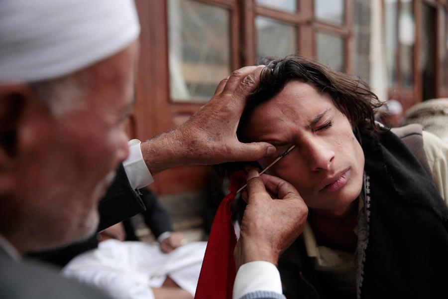 Человек наносит косметическое средство сурьма или кохл на веко в соборной мечети старого города Сане, Йемен, 23 июня 2016 года. Кохл используется на Ближнем Востоке в качестве защиты от глазных болезней.