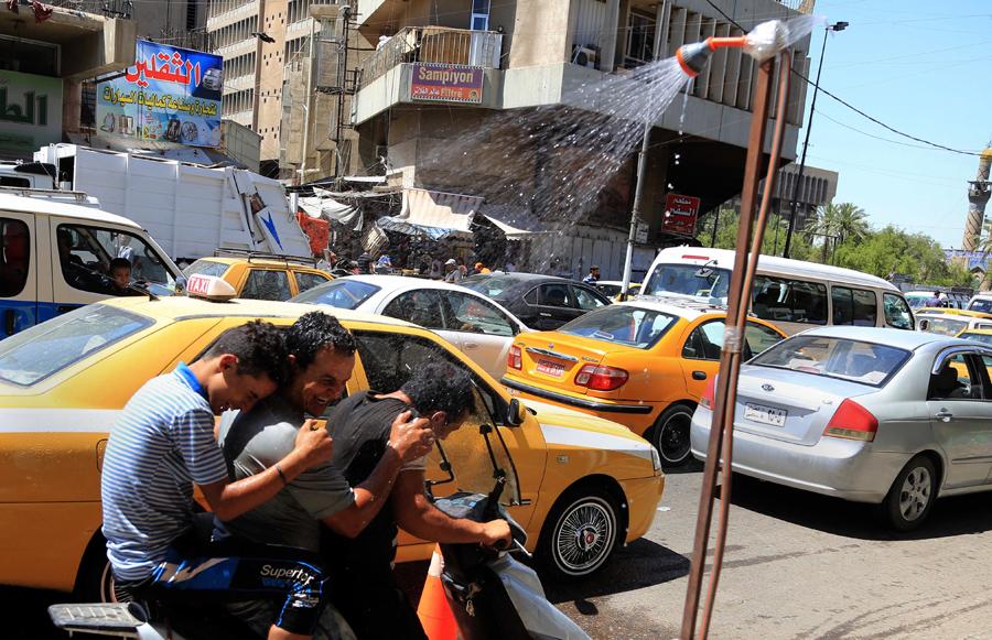 Трое молодых людей пользуются общественным душем, чтобы остыть от летней жары во время Рамадана, когда ревностные мусульмане воздерживаются от пищи и воды в дневное время, Багдад, Ирак, 11 июня 2016 года.