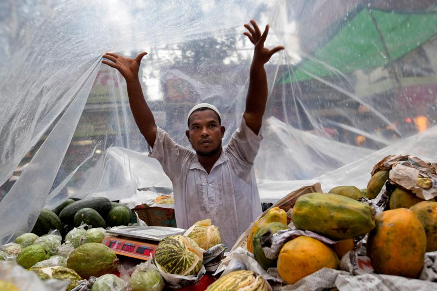 Придорожный продавец фруктов в Бангладеше покрывает свой прилавок прозрачной плёнкой в Дакке, Бангладеш, 7 июня 2016 года.