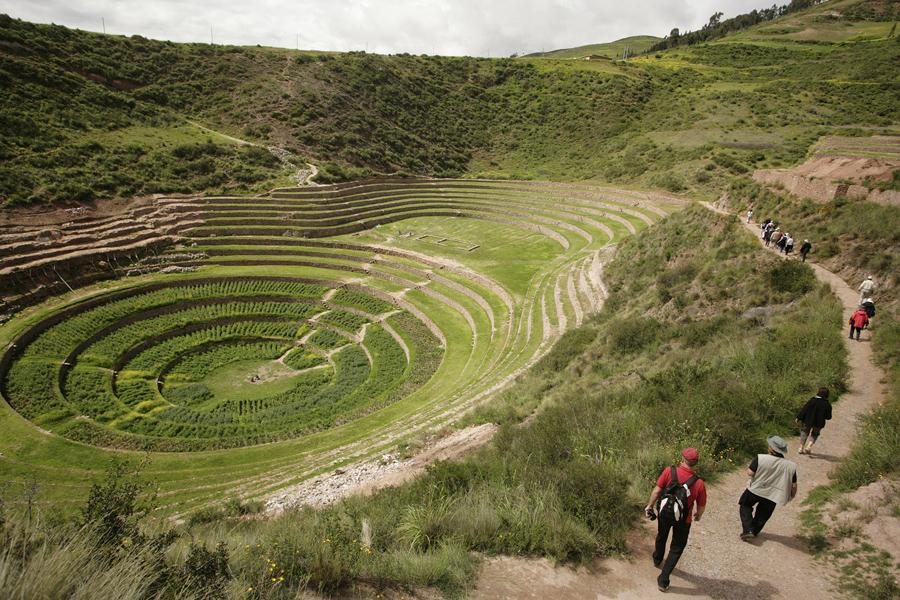 Туристы идут до террас инков Морей недалеко от города Мараш в Куско, Перу.