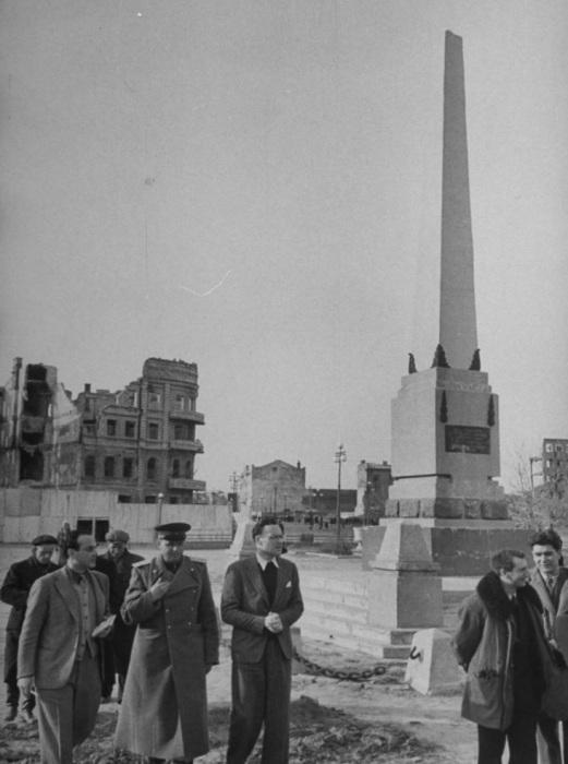 Корреспонденты, осматривающие разрушенный город