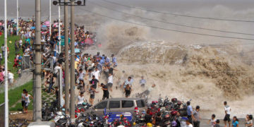 A crowd of Chinese tourists run away as a tidal bore breaks through the dam by the Qiangtang River in Haining, east China's Zhejiang province on August 31, 2011. Visitors gather to experience the Qianjiang Tidal Bore from early morning, an annual tradition for the residents living nearby. CHINA OUT AFP PHOTO (Photo credit should read STR/AFP/Getty Images)