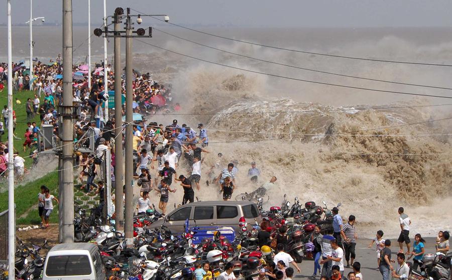 Толпа китайских туристов убегает от приливной волны вдоль реки Цяньтан в Ханчжоу, Китай, 31 августа 2011 года.