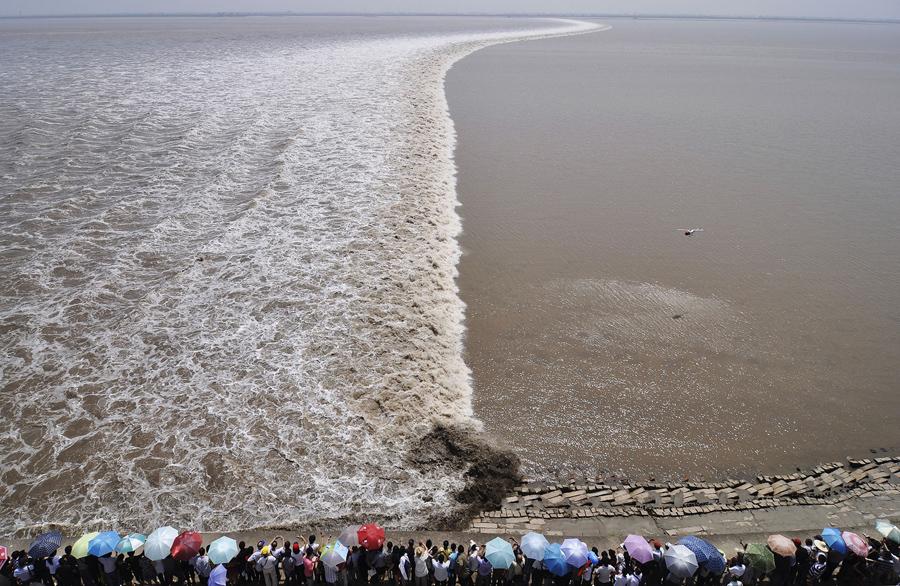 Фотография с вертолёта который парит над рекой Цяньтан. Туристы собираются на берегу чтобы увидеть прилив, 13 сентября 2011 года.