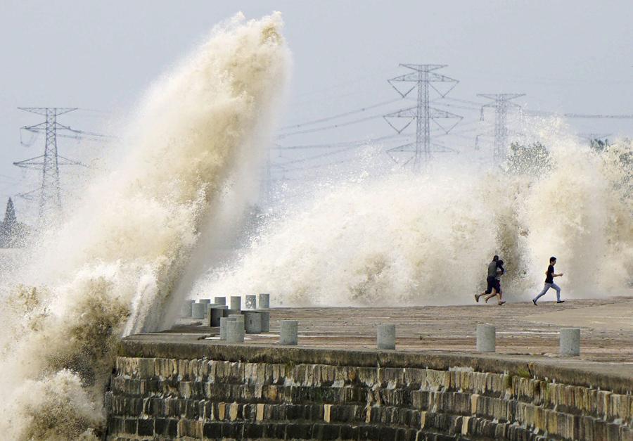Люди бегут от воды вызванных приливной волной которая хлынули мимо барьера на берегу реки Цяньтан, в Ханчжоу, 8 октября 2014 г.