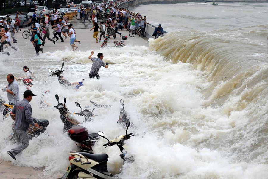 Люди охвачены огромными волнами, наблюдая приливы на реке Цяньтан, 15 августа 2014 г.