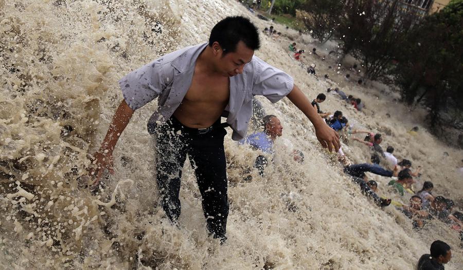 """Зрителей уносит вниз холма огромными волнами в Ханчжоу, в этом сезоне волны выросли выше чем обычно из - за влияния тайфуна """"Трами"""", в восточной провинции Китая, 22 августа 2013 г."""