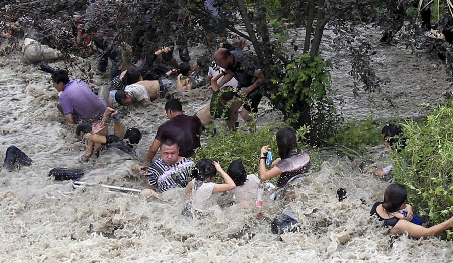Люди изо всех сил пытаются встать на ноги после того как их смыло вниз с холма огромными волнами, 22 августа 2013 г.