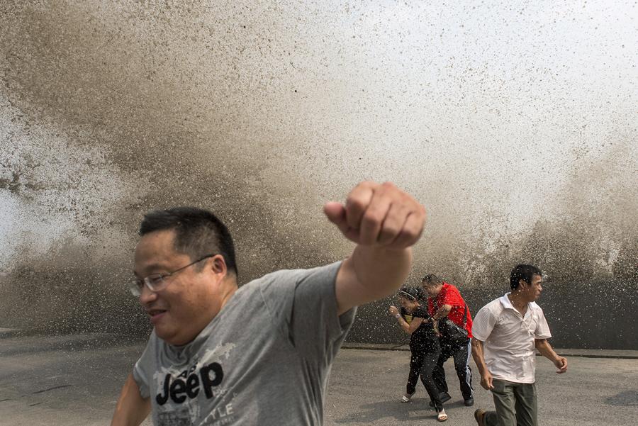 Люди бегут от приливной волны которая хлынула над барьером на берегу реки Цяньтан, в Ханчжоу, Китай, 30 августа 2015 года.