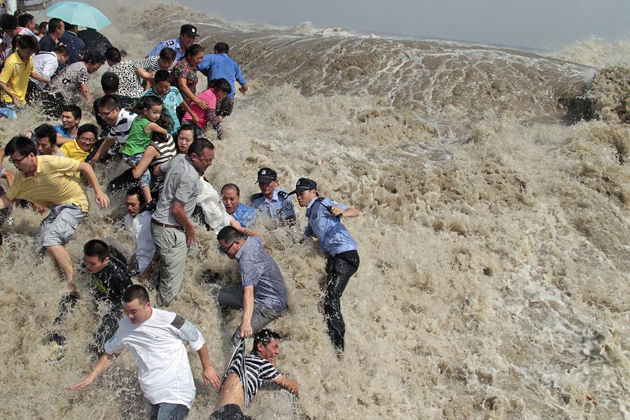 Полицейские и жители стараются держаться на ногах от приливной волны, 31 августа 2011 года.