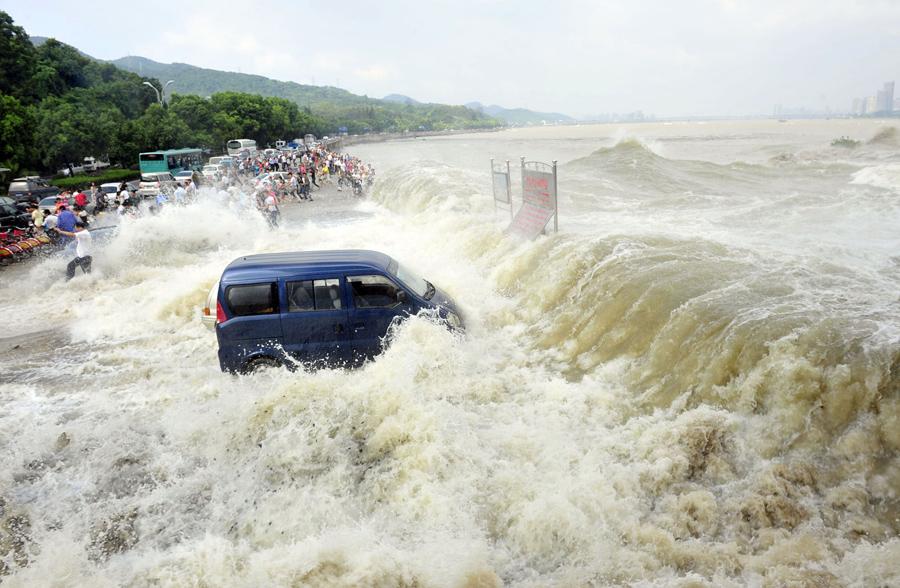 Люди убегают от приливной волны на берегу реки Цяньтан, 31 августа 2011 года.