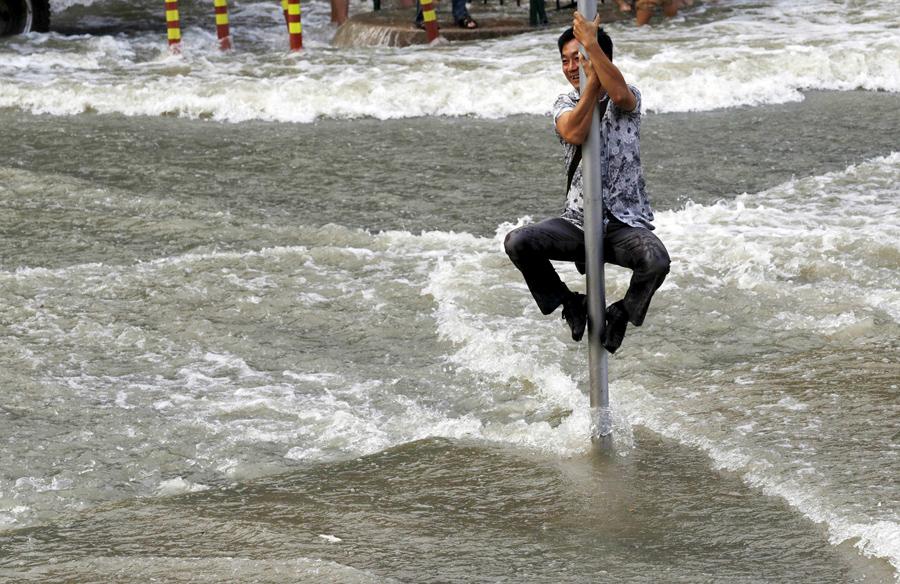 Китаец зацепился за дорожный знак что бы не унесло волнами, 1 сентября 2015 года.