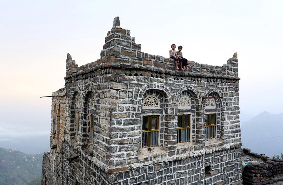 Мальчишки сидят на краю крыши своего дома в горах, в западной провинции Райма, Йемен, 31 мая 2016 года.