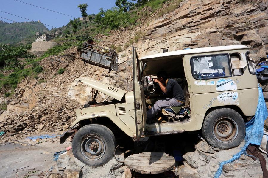 Мужчина использует автомобильный двигатель для запуска канатной дороги , которая поднимает людей и грузы до горы Dhalamlam, 20 мая 2016 года.