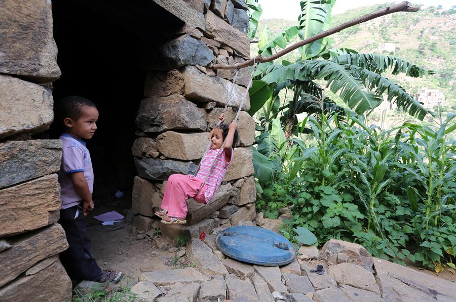 Девочка качается на качелях возле своего дома в горах западной провинции Йемена в Райме, 3 июня 2016 года.