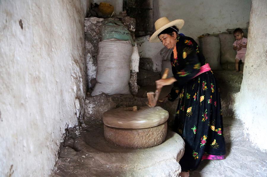 Женщина использует каменную дробилку для изготовления муки в своем доме, 21 мая 2016 года.