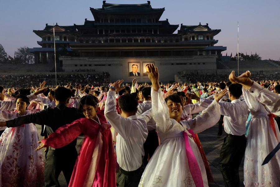 Студенты танцуют во время мероприятия в честь Ким Ир Сена на площади Пхеньяна, 1 мая 2015 года.