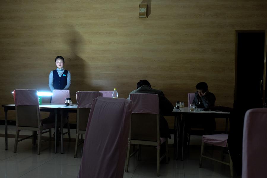 Официантка ставит лампу на батарейках на стол во время отключения электроэнергии в Чхонджине, 23 апреля 2015 года.