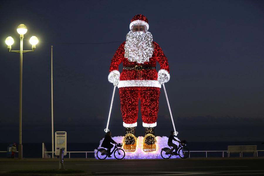 """Велосипедисты проезжают мимо гигантской светящейся модели Санта - Клауса, вдоль """"Английской набережной"""" в городе Ницца на юго - востоке Франции, 9 декабря 2016 года."""