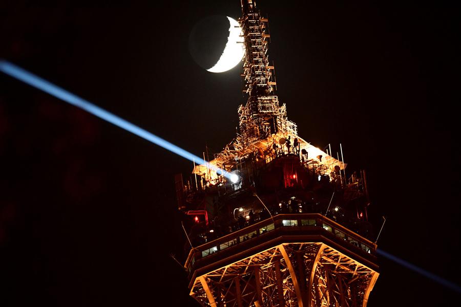 Луна рядом с верхушкой освещенной Эйфелевой башни, 5 декабря 2016 года в Париже.