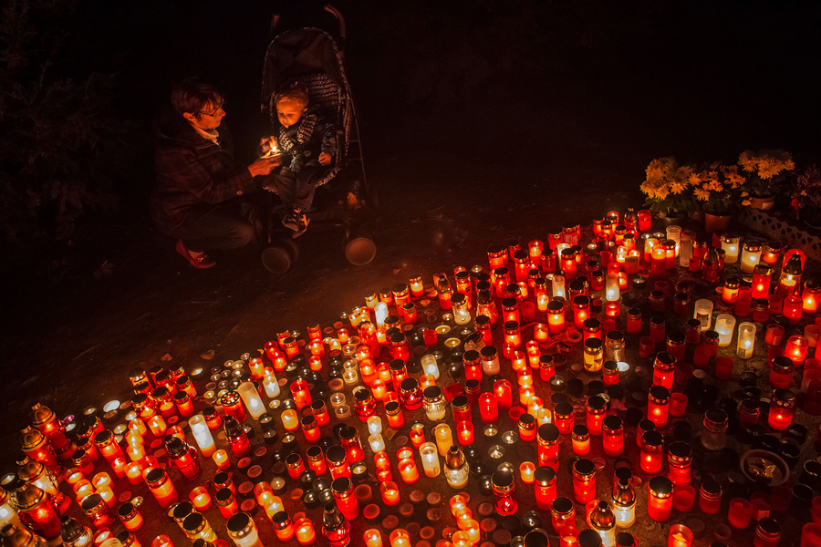 Женщина с ребенком зажигают свечи на Олшанском кладбище, 1 ноября 2016 года в Праге, Чехия. Многие чехи посещают кладбища во время Дня Всех Святых чтобы выразить дань уважения умершим родственникам зажечь свечи и возложить цветы.