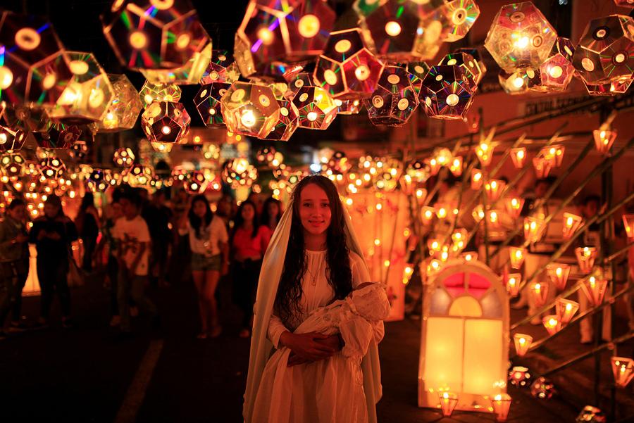 Девушка одетая как Дева Мария позирует для фотографа во время праздника фонарей накануне Рождества Девы Марии в Ауачапане, Эль-Сальвадор, 7 сентября 2016 года.