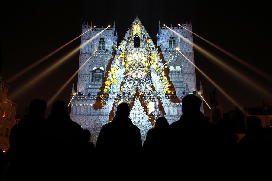 Люди смотрят изображение проецирующее на здание во время ночного светового шоу в Лионе, центральная Франция, 8 декабря 2016 года.