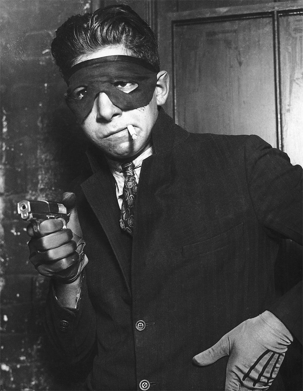 Молодой человек, выдает себя за замаскированного бандита.
