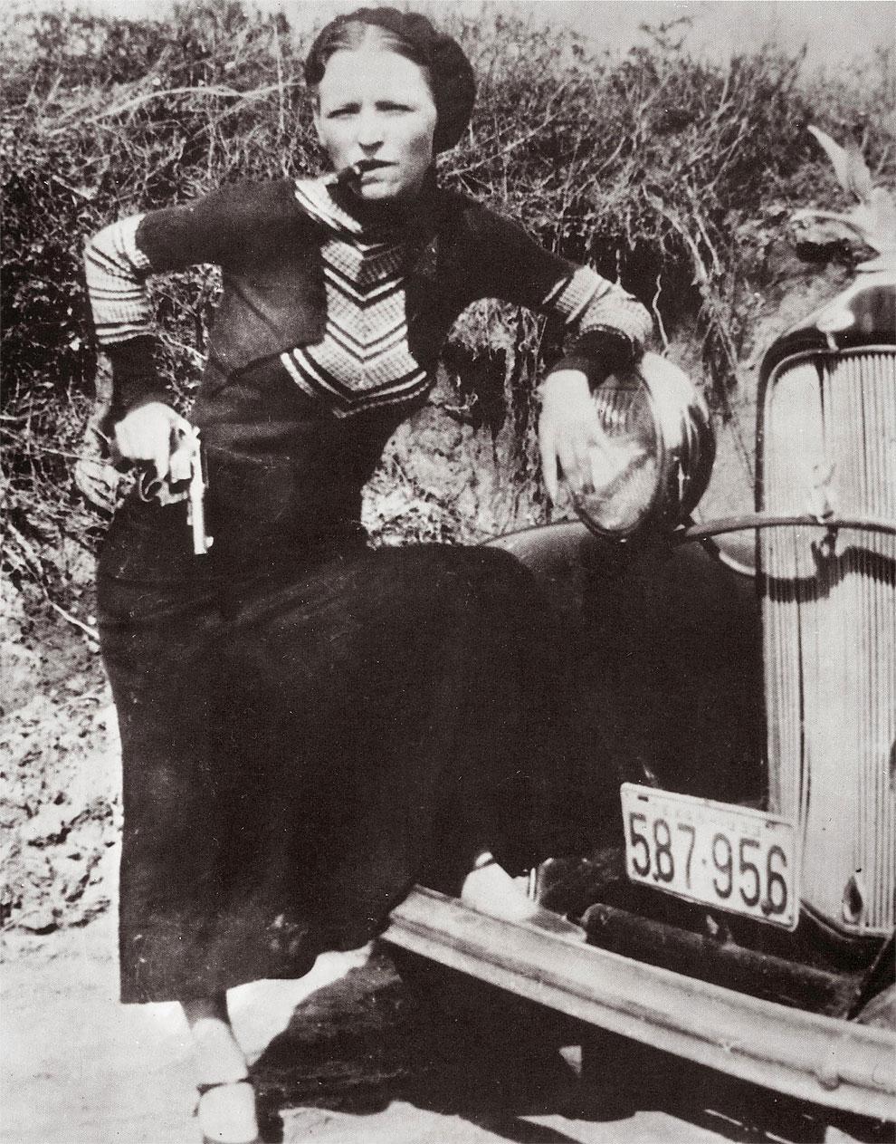 Бонни Паркер (1910 - 1934) опираясь на автомобиль курит сигару с пистолетом в руке 17 апреля 1933 года.