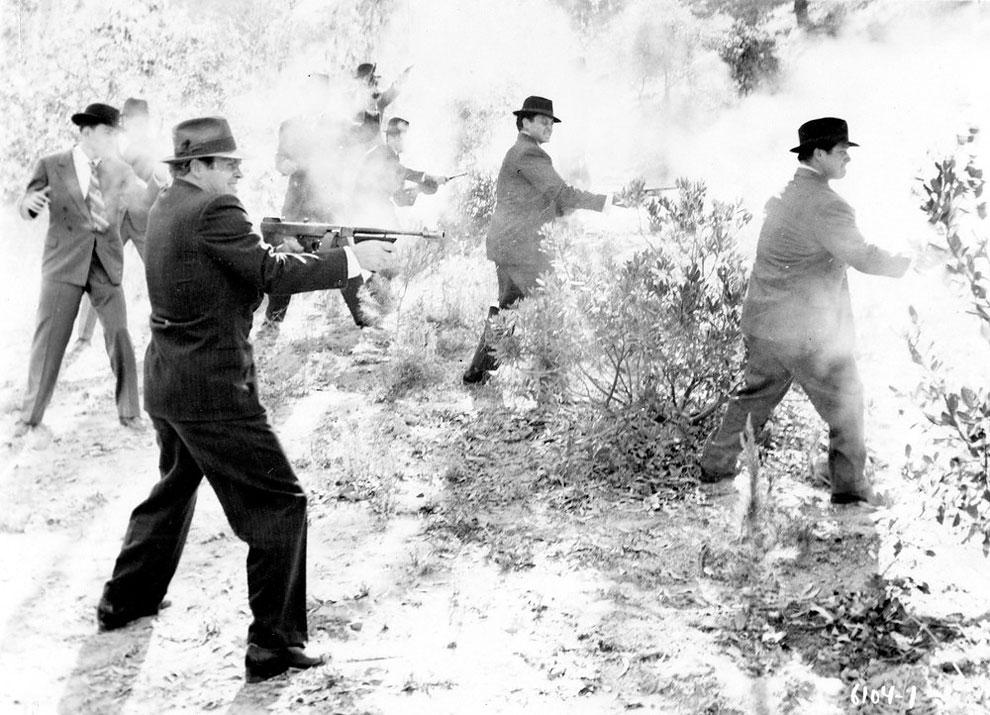 Группа гангстеров в костюмах и головных уборах тренируются в стрельбе из Томпсона, пистолетов - пулеметов, дробовиков и револьверов, США, 1930 - е годы.