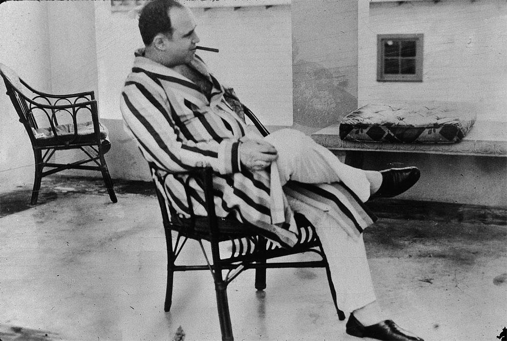 """Американский гангстер Аль Капоне ( """"Scarface"""") (1899 - 1947) отдыхает в своем доме в Майами, Флорида, 1930 г. Капоне курит сигары и носит полосатый халат."""