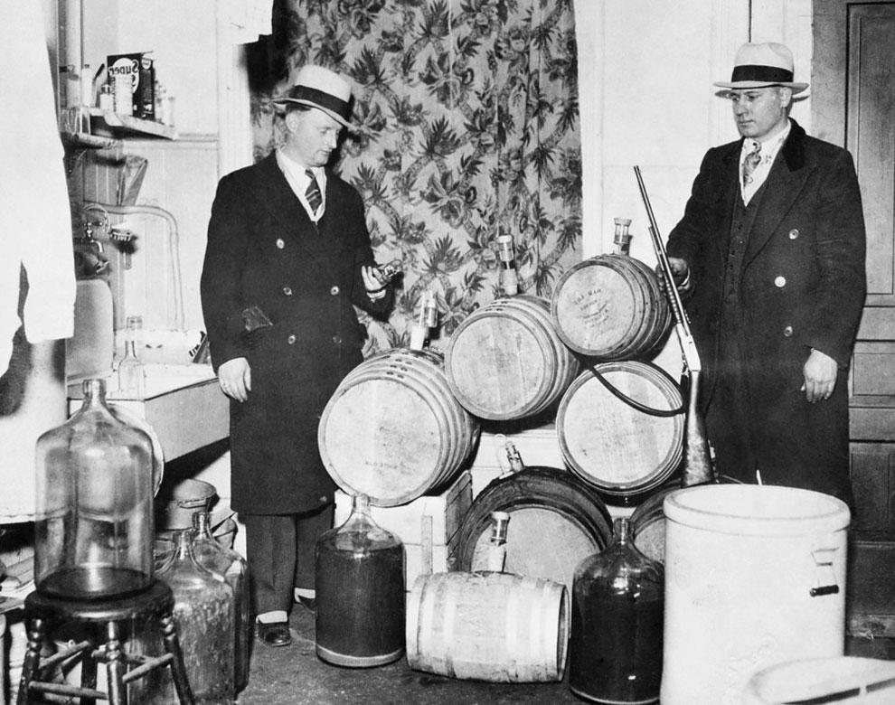 Полицейские смотрят на перегонное оборудование, конфискованные во время сухого закона, Чикаго, 1920 год.