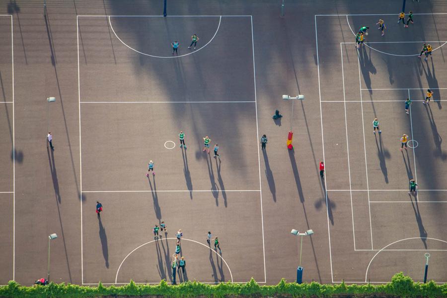 Дети и взрослые играют на спортивной площадке в Лондоне.