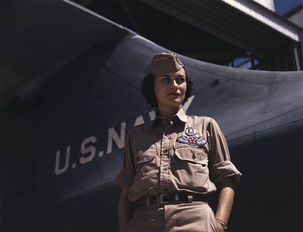 Девушка стоит возле хвоста самолета военно-морского флота на Авиабазе Военно морского флота, Корпус-Кристи, штат Техас, август 1942 г.