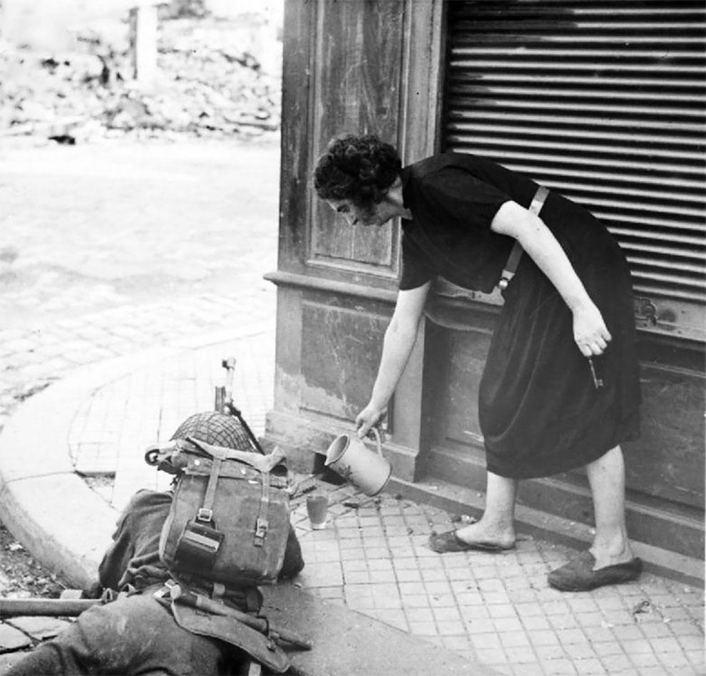 Француженка наливает британскому солдату чашку чая во время боевых действий, после высадки союзников в Нормандии, 1944 г.