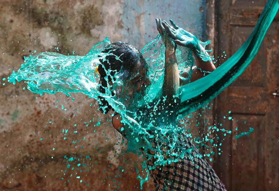 Девушка попала под струю покрашенной воды во время празднования Холи, фестиваль цветов, в Мумбаи, Индия