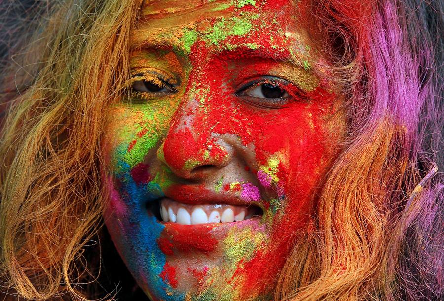 Студентка с цветным порошком на лице, во время праздника около университетского городка в Калькутте, Индия.