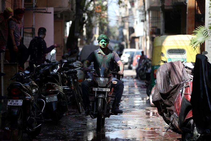 Мужчина с зеленым порошком на лице едет на мотоцикле во время Холи в Дели, Индия, 13 марта, 2017.