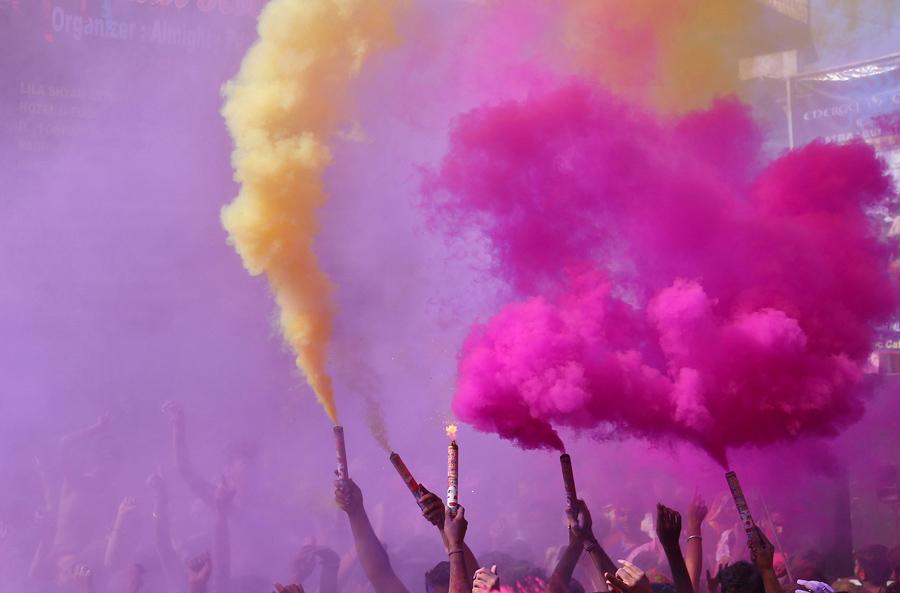 """Люди зажигают цветные """"дымовухи"""" в Пушкаре штат Раджастан, Индия, 13 марта, 2017."""
