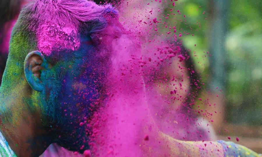 Индийские студенты обдают друг друга цветными порошками, так они празднуют Холи в Калькутте, 13 марта 2017 года.