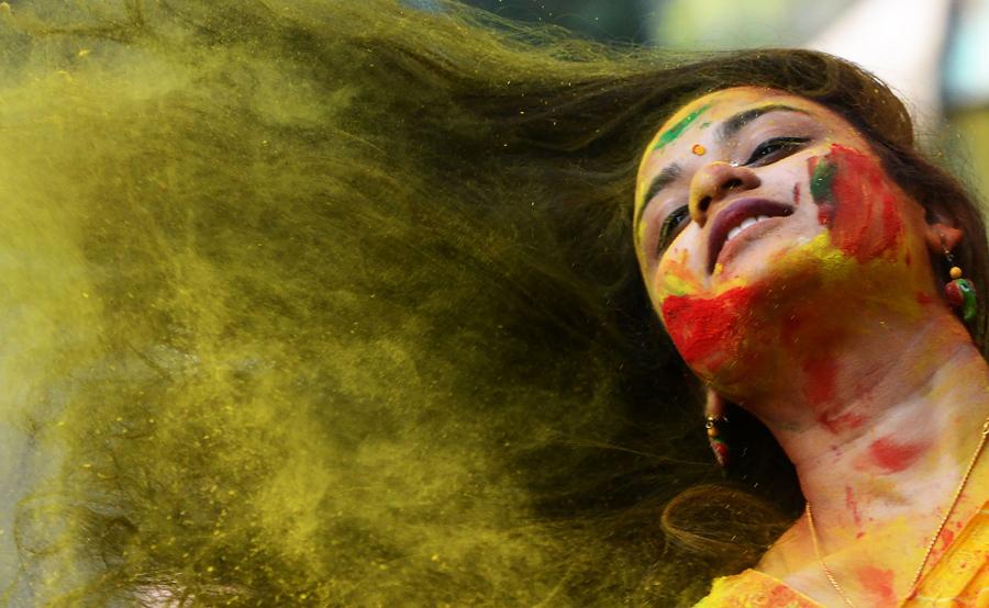 Индийская девушка в цветном порошке, в Калькутте 13 марта 2017 года.