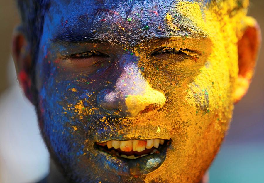 Мальчик с цветным порошком на лице.